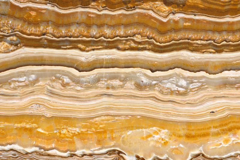 Real natural pattern of ONYX Onice Empire Gold texture background. Natural pattern of onyx beige color polished slice mineral. Super high resolution. ONYX Onice stock photography