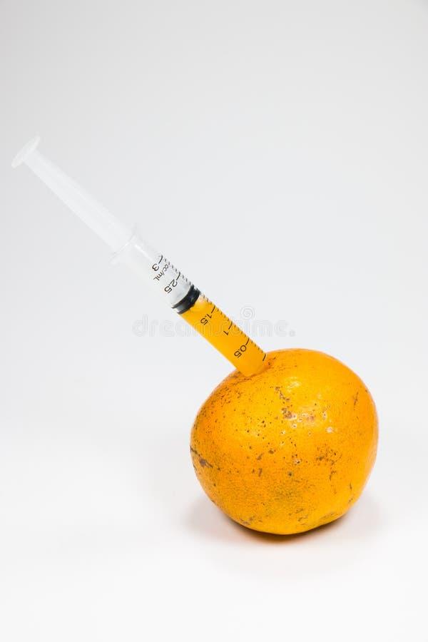 Real orange fruit was sucked by syringe stock photo