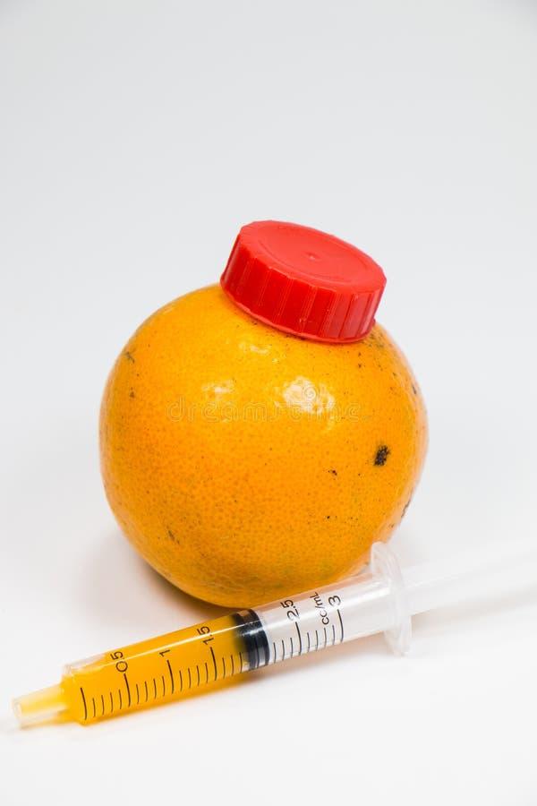 Real orange fruit was sucked by syringe royalty free stock photo