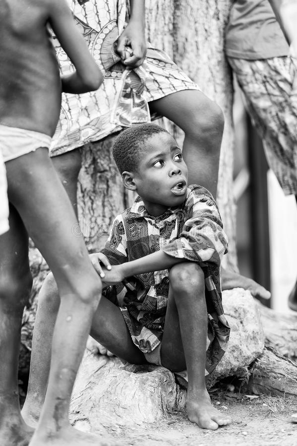 Real people in Togo, in black and white. KARA, TOGO - MAR 9, 2013: Unidentified Togolese boy sits among other kids. Children in Togo suffer of poverty due to the royalty free stock image