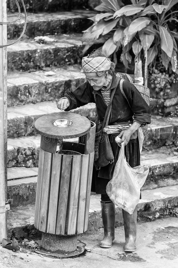 Real people in Vietnam, in black and white. LAO CHAI, VIETMAN - SEP 22, 2014: Unidentified Black Hmong woman checks a trash bucket in Lao Chai, Vietnam. Hmong is royalty free stock photography