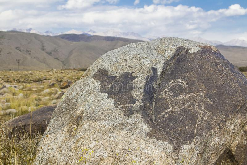 Real petroglyphs on natural stone found in the steppe, on a blurred background of beautiful mountains stock photos