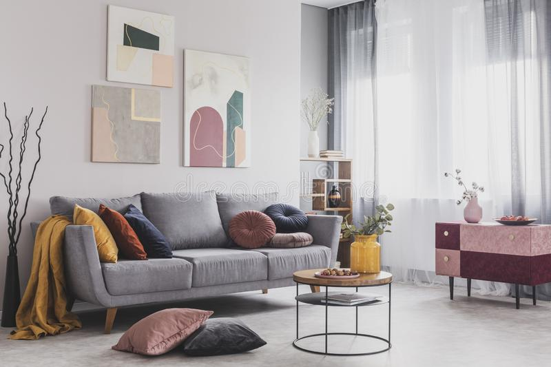 Abstract paintings hanging on white wall above a gray sofa in a living room interior with big windows. Real photo of abstract paintings hanging on white wall royalty free stock images