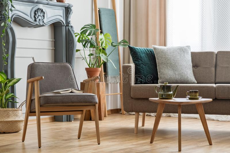 Real photo of an armchair with a book standing next to a small t. Able with pot and sofa with cushions in cozy living room interior with plants concept royalty free stock photos