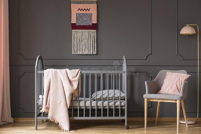 Real photo of a baby crib with a blanket standing next to an arm. Chair with a cushion and a lamp in child`s room interior royalty free stock photos