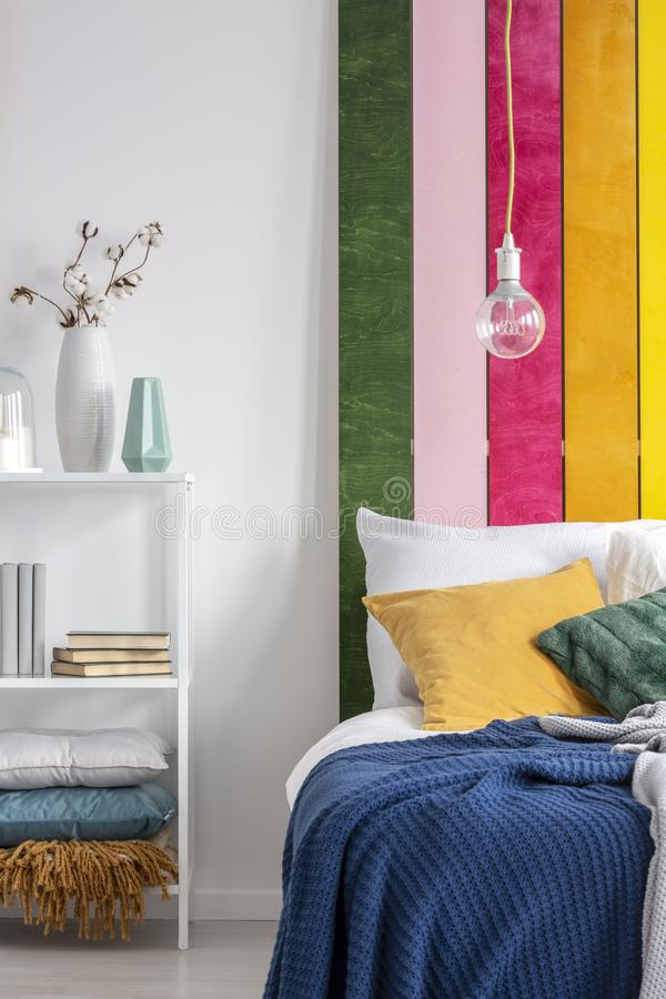 Real photo of a bare light-bulb hanging above a white bed with yellow pillow and blue blanket in folk bedroom interior. Bare light-bulb hanging above a white bed royalty free stock image