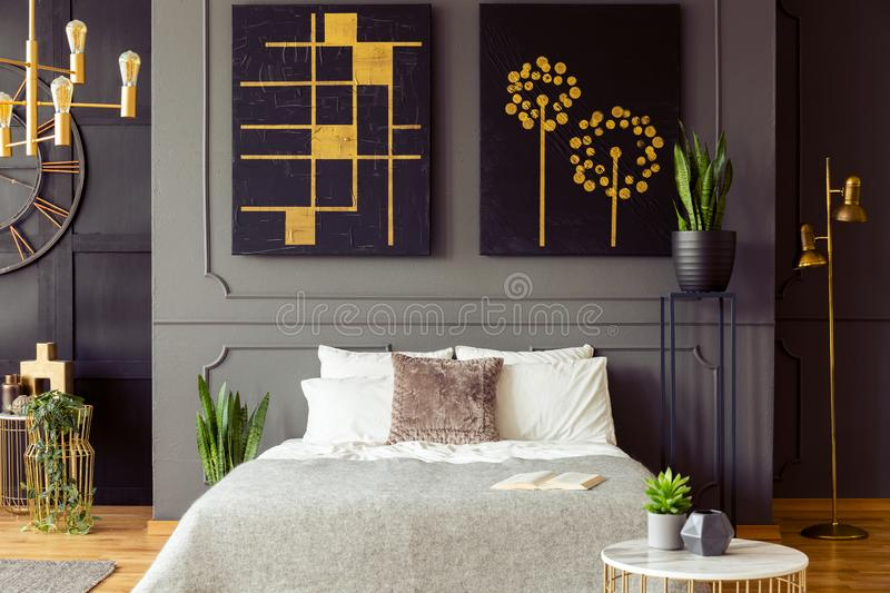 Real photo of a bedroom interior with big, black paintings with golden accents, double bed and plants. Concept royalty free stock photos