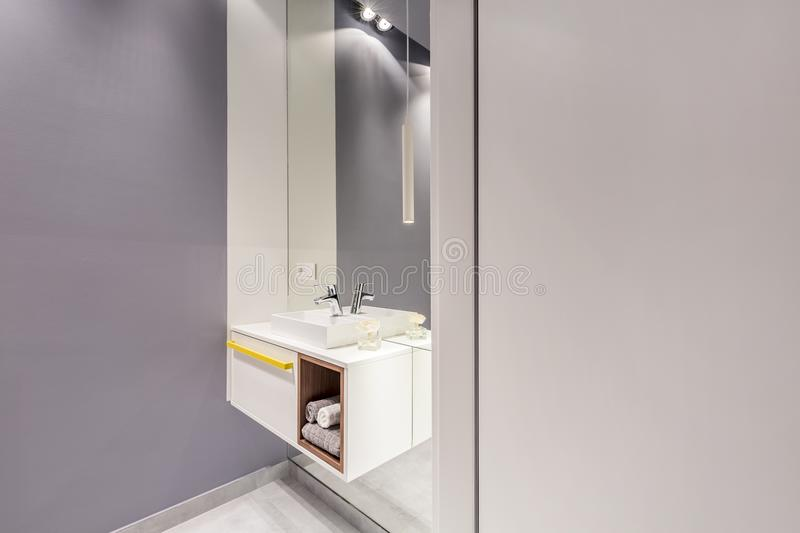 Big mirror and white cupboard with towels and sink in grey bathroom interior with empty walls for your posters. Real photo of big mirror and white cupboard with stock images