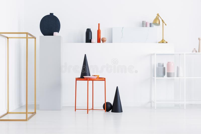 Black cone, pink plate, orange coffee cup on metal table on display of shop with modern art. Real photo of black cone, pink plate, orange coffee cup on metal stock photography