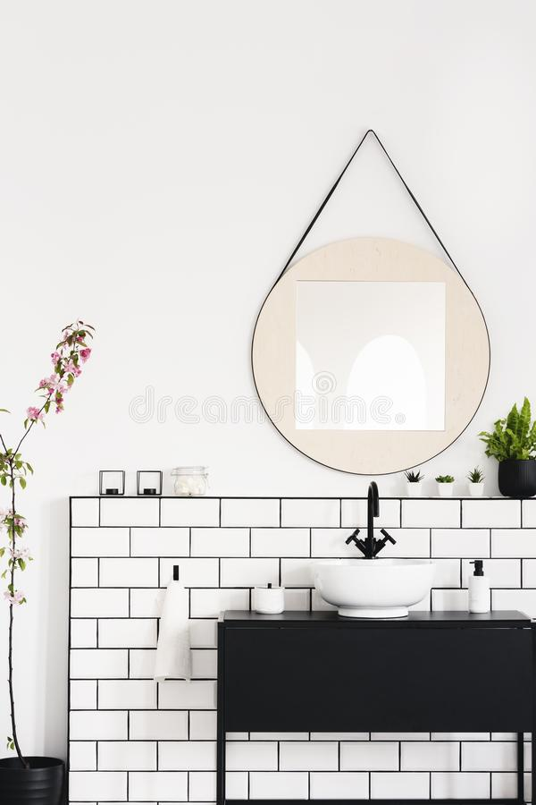 Real photo of a black cupboard, round mirror and white tiles in a modern bathroom interior stock photos