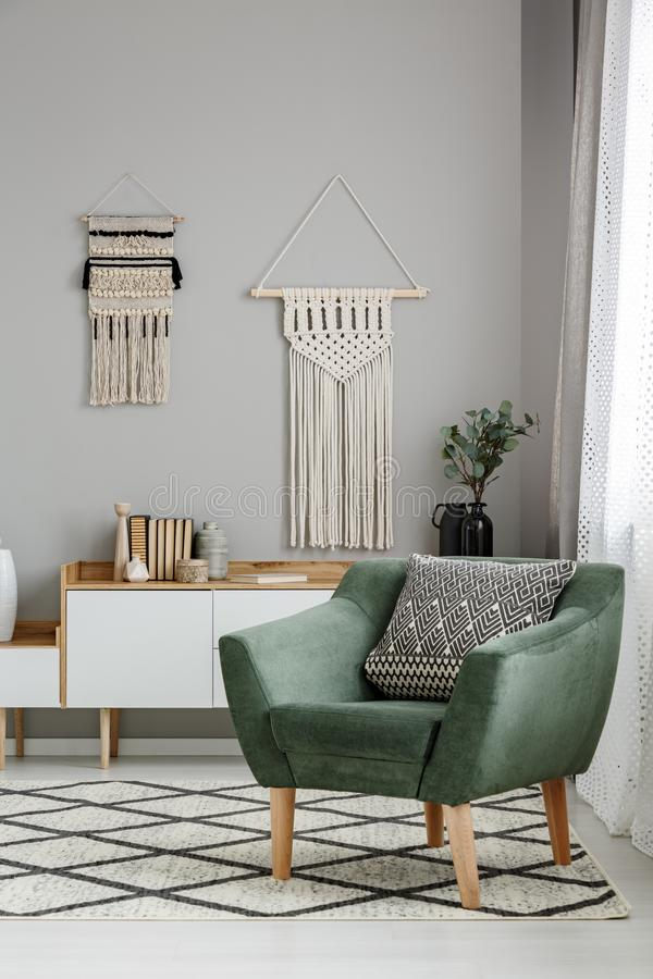 Real photo of a boho living room interior with macrame hanging o royalty free stock image
