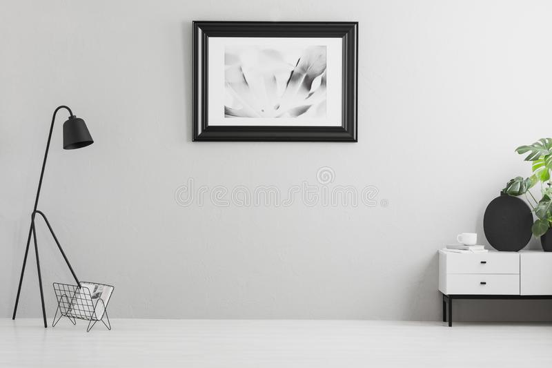 Real photo of bright grey living room interior with simple poster, metal lamp, white cupboard and empty place for your couch. Concept royalty free stock photography