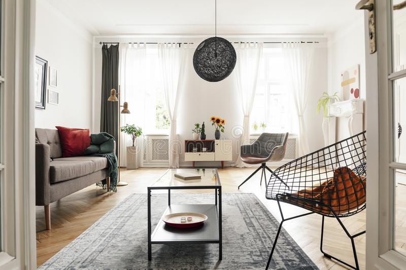 Bright living room interior with a metal armchair, coffee table and sofa. Big lamp in the middle. View through a d. Real photo of a bright living room interior royalty free stock photos