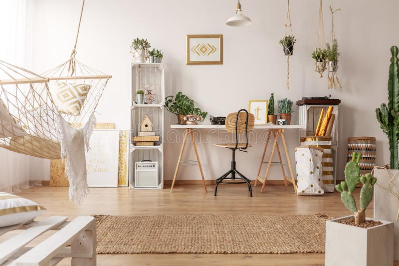 Bright room interior with hammock, fresh plants and home office corner with wooden desk, chair and decor stock image