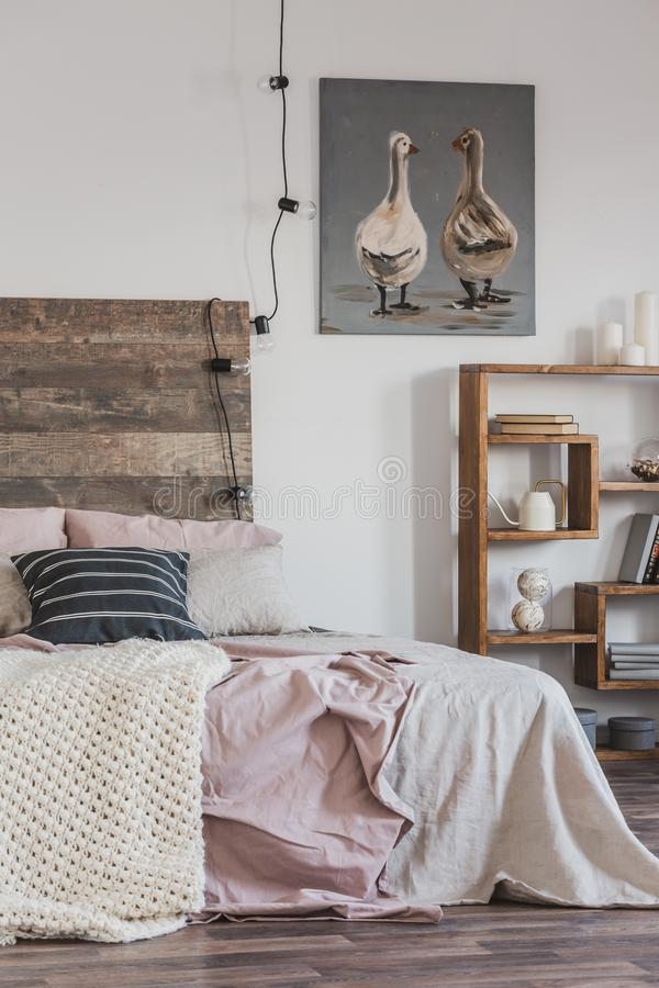 Real photo of a bright, rustic bedroom interior with pink bed, wooden furniture and painting of two ducks. Real photo of a bright, rustic bedroom interior with stock photo