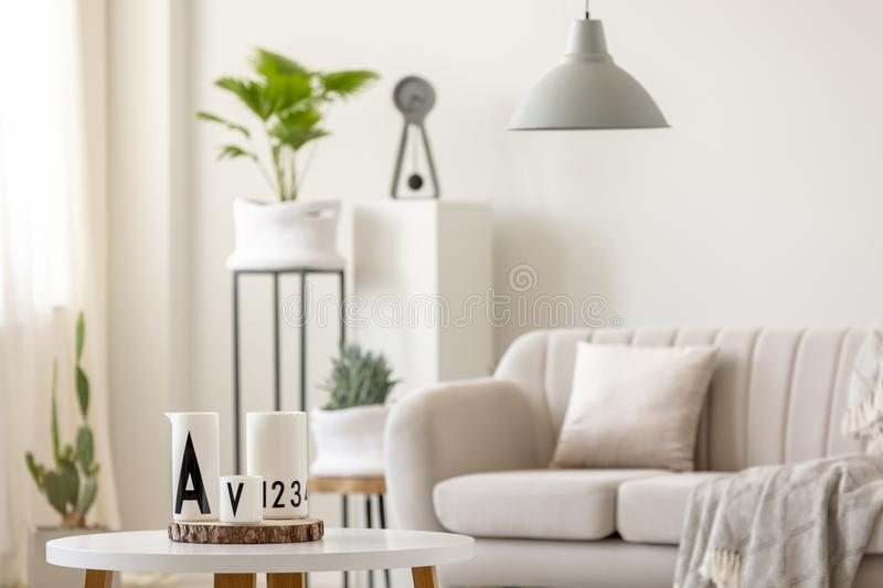 Real photo of ceramic jugs standing on a table in front of a blu. Rred couch, lamp and plants in white living room interior stock photography