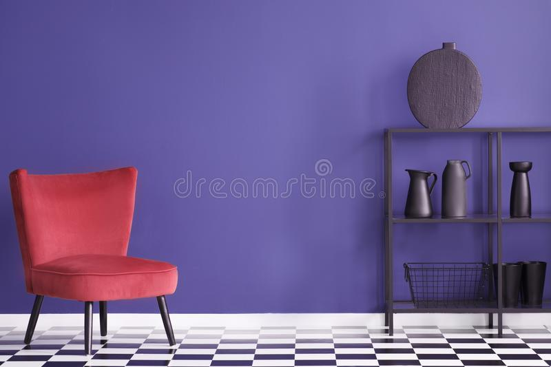 Real photo of a colorful living room interior with red, velvet a. Rmchair and black rack with decorations against an ultra violet wall stock photography