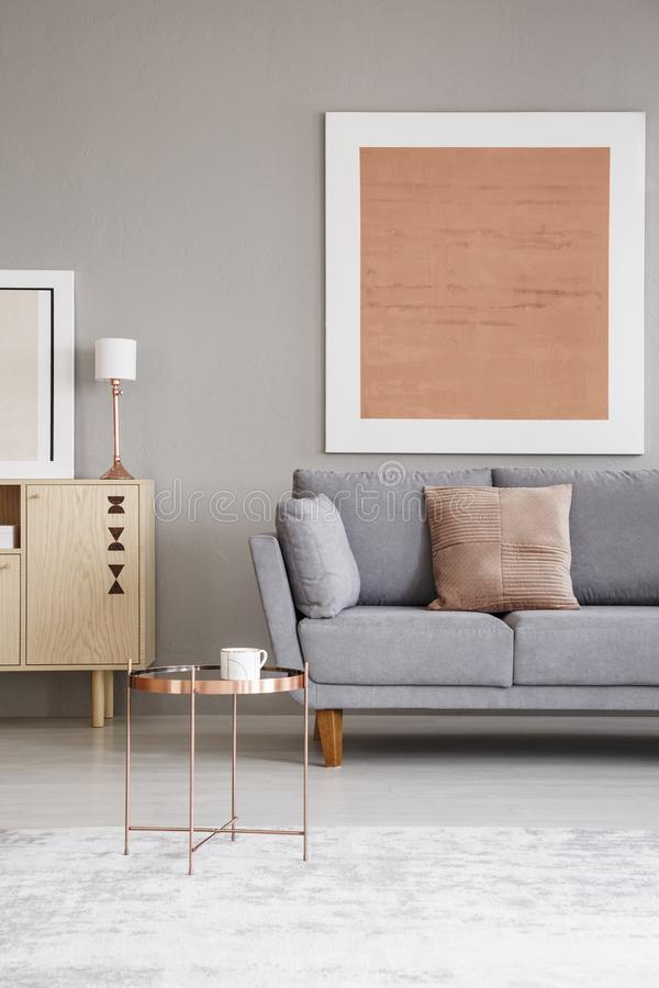 Copper table in a living room interior with a modern painting on a wall and sofa. Real photo of a copper table in a living room interior with a modern painting royalty free stock image