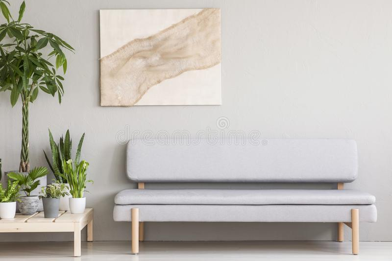Real photo of a cozy gray couch standing next to a wooden platform with plants in a simple, scandi living room interior stock images