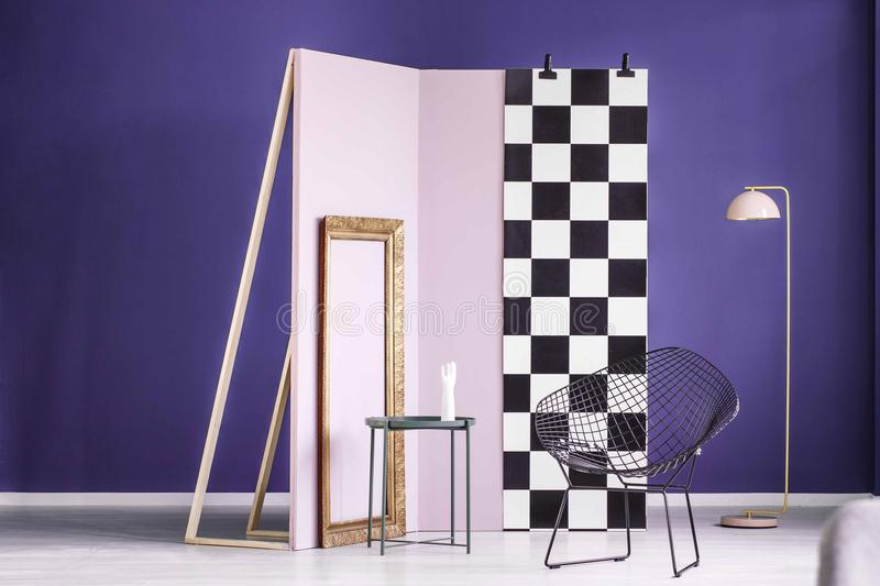 Real photo of a creative arrangement of furniture in purple interior with gold frame, metal table, black chair and lamp stock image