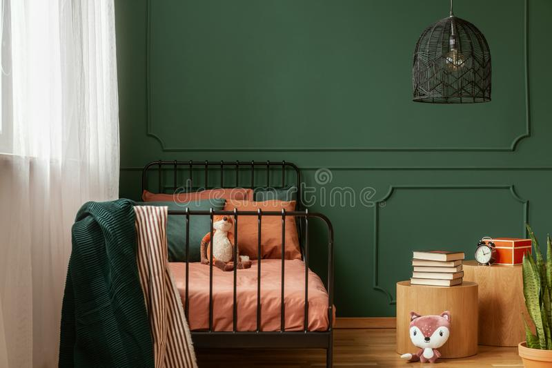 Real photo of a cute, green and orange bedroom interior for a kid with plush fox toys, molding on green wall and books on bedside stock image