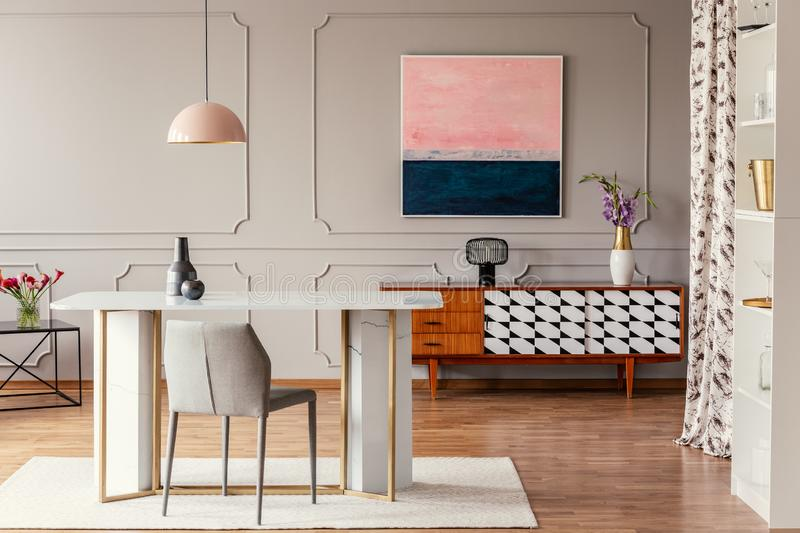 Dining room interior with a table, pink painting and vintage cabinet. Real photo of a dining room interior with a table, pink painting and vintage cabinet stock image
