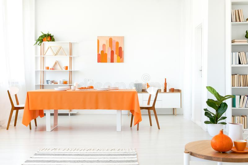 Real photo of dining room in vivid color. Orange tablecloth on long table with white chairs stock photo
