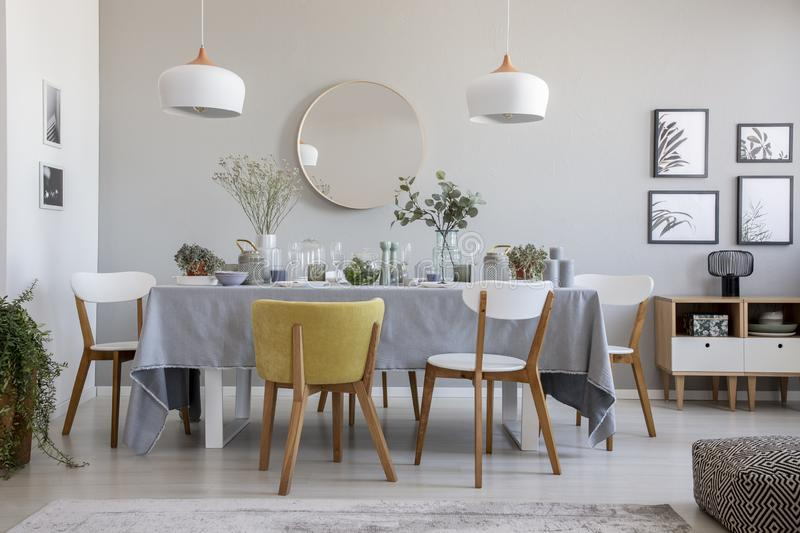 Elegant dining room interior with a laid table, chairs, mirror on a wall and lamps stock image