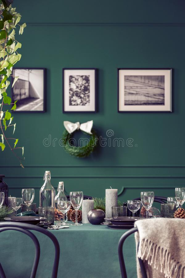 Real photo of an elegant dining room interior prepared for a family Christmas celebration. Plates and glasses on a green cloth. Real photo of an elegant dining stock image