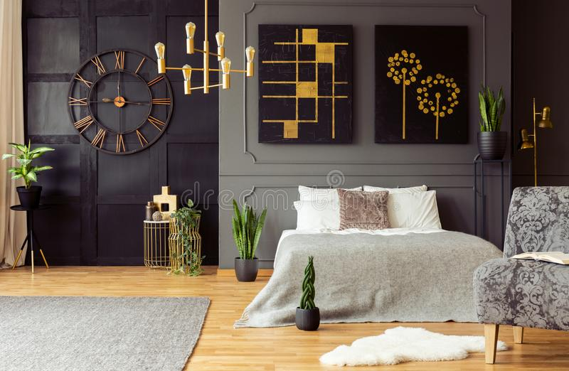Real photo of golden accents, clock, paintings, plants and double bed in a dark bedroom interior. Concept royalty free stock images