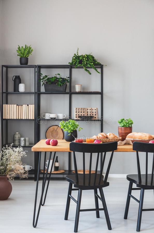 Real photo of a grey dining room interior with metal shelves, dining table with food and chairs. Concept royalty free stock image
