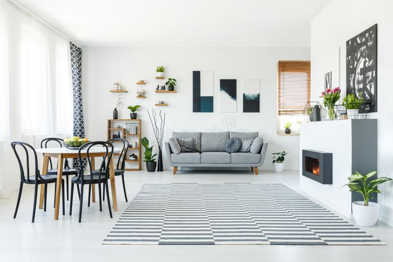 Real photo of a grey sofa standing in spacious living room with. Bio fireplace, table with chairs, wooden shelves, plants and paintings on the walls royalty free stock images