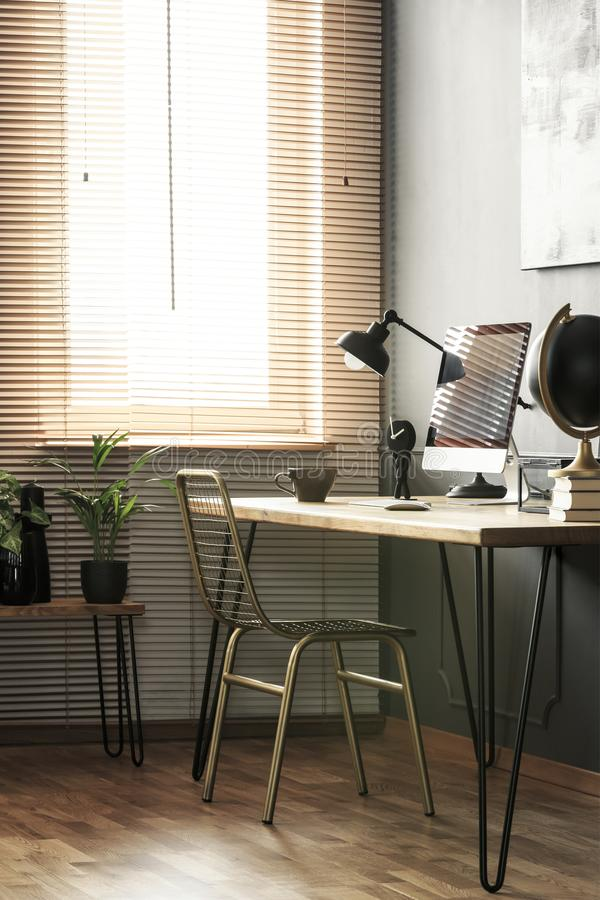 Real photo of hairpin desk with lamp, home office computer and c. Offee cup standing in living room interior with gold chair and window with blinds stock photography