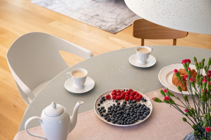 Real photo with high angle of dining table with fresh flowers, jug, coffee cups and plate with fruits. Concept royalty free stock photo