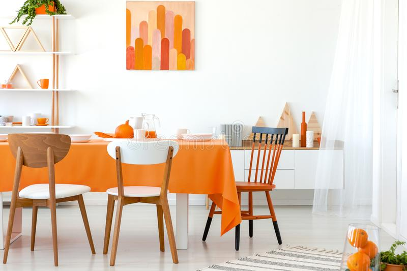 Kitchen table covered with orange tablecloth and white dishes. Artwork on the wall and shelf in the corner royalty free stock image