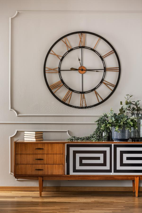 Real photo of a large, metal clock hanging on a white wall with molding above a wooden cupboard in bright living room interior royalty free stock image
