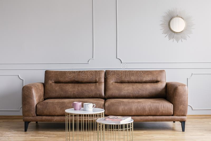 Leather sofa, coffee tables and mirror in a living room interior royalty free stock photos