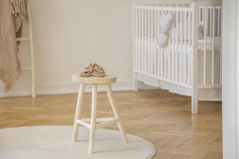 Little baby shoes placed on wooden stool standing in white kid room interior with crib, round rug and herringbone pa. Real photo of little baby shoes placed on royalty free stock photo