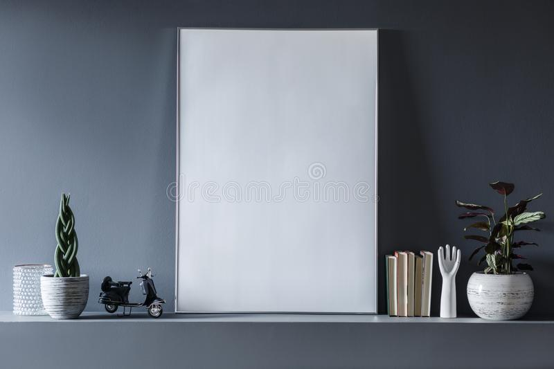Real photo of a mockup poster standing on shelf between plants a stock photography