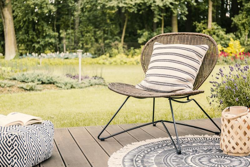 Real photo of a modern garden chair with a white, striped pillow. Standing on a wooden deck in the garden of a weekend retreat royalty free stock images