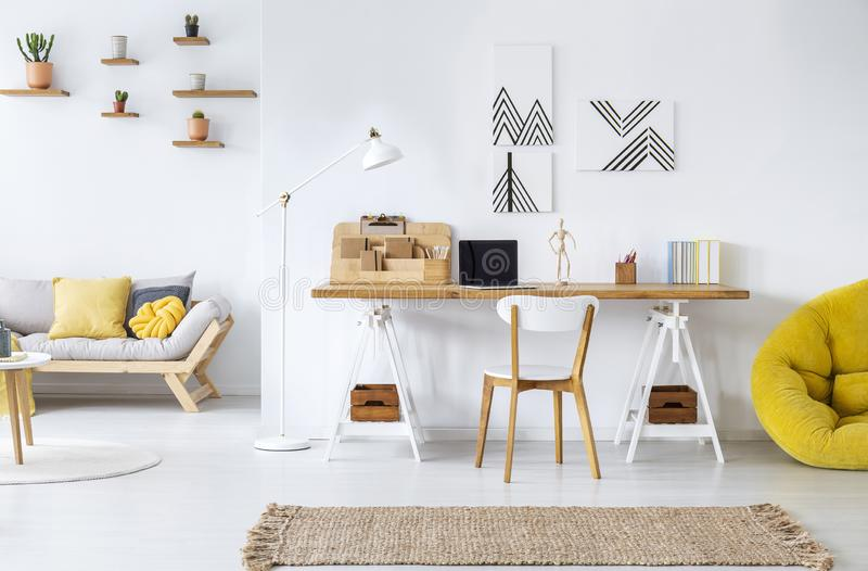 Modern home office interior with graphics, desk, sofa and yellow pouf. Real photo of a modern home office interior with graphics, desk, sofa and yellow pouf royalty free stock photo