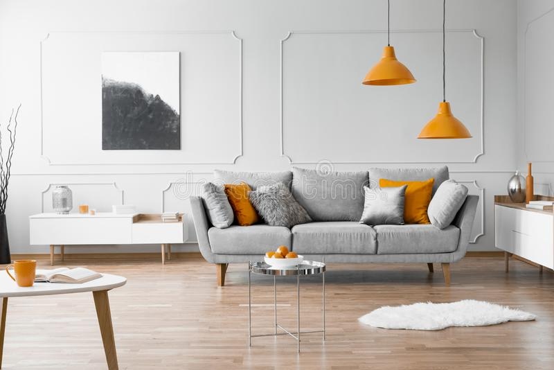 Photo of a modern living room interior with a sofa, orange lamps and painting. Real photo of a modern living room interior with a sofa, orange lamps and painting royalty free stock photography