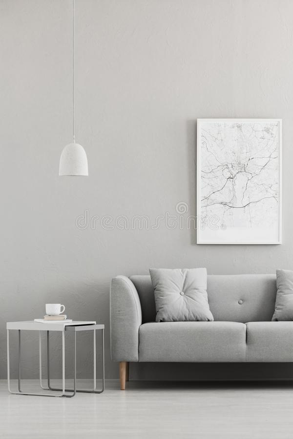 Free Real Photo Of Map Poster Hanging On The Wall In Living Room Interior With Grey Sofa, Metal End Table With Books And Coffee Cup And Royalty Free Stock Photography - 125437207