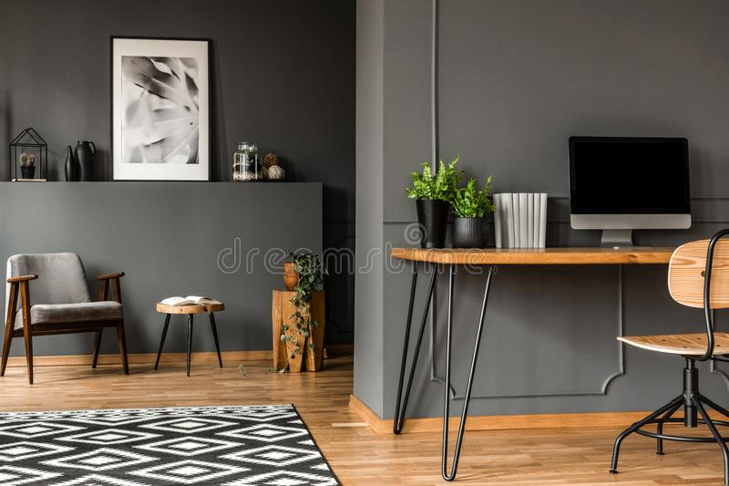 Real photo of open space home interior of a freelancer with simple workspace at the front and a living room with gray armchair in stock photo