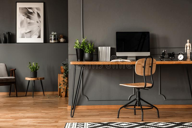 Real photo of an open space interior with black walls and molding. Workspace with desk, chair and computer in the foreground and stock photography