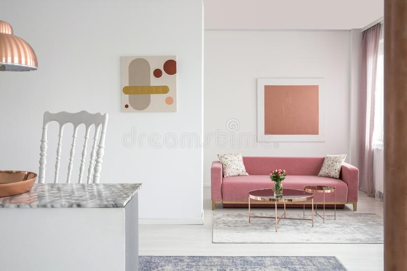 Real photo of paintings in a spacious living room interior with a pink sofa and copper coffee table. Concept royalty free stock photo