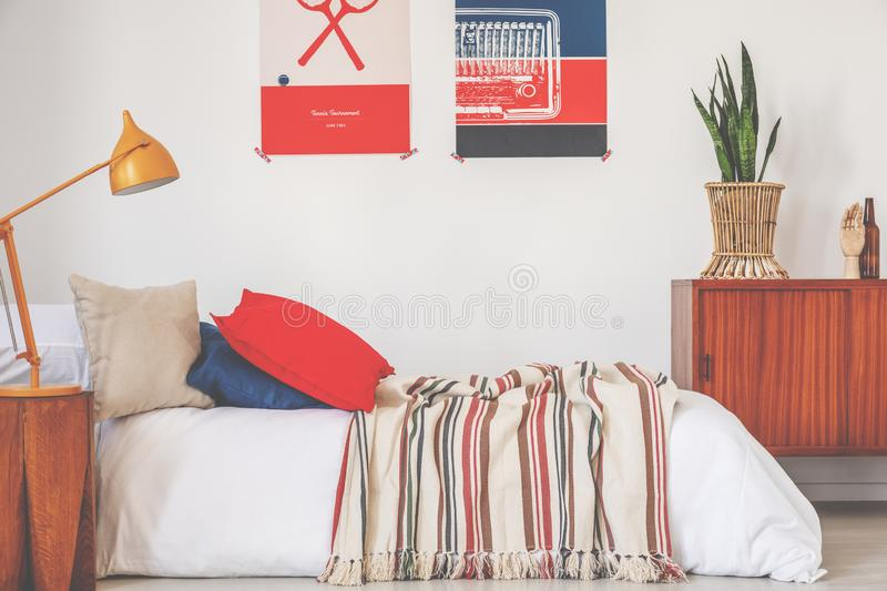 Real photo of a red and blue bedroom interior with a bed, lamp and posters.  stock photos