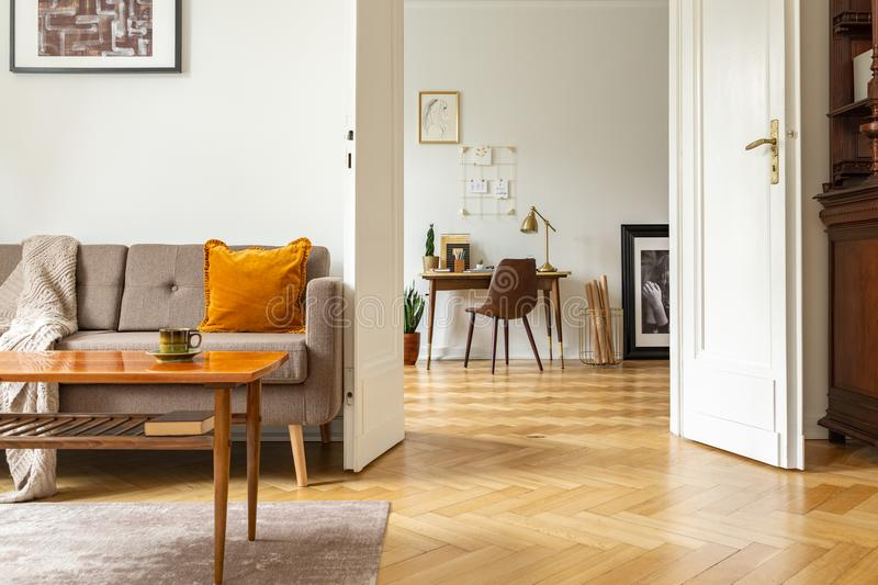 Real photo of a retro living room interior and view of a home office. View through a door. Concept stock photos