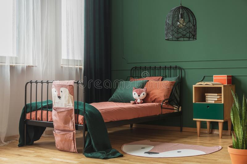 Real photo of a rug shaped like a fox on the wooden floor of a child`s bedroom interior with orange sheets and pillows on a black. Real photo of a rug shaped royalty free stock photos