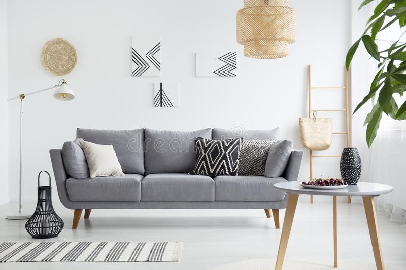 Real photo of a scandi living room interior with cushions on gray couch, cherries on wooden table and bag on a ladder royalty free stock images